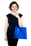 Young shopaholic woman carrying bright bag Stock Photo