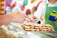 Young shopkeeper at work selling sweets to customer Royalty Free Stock Photography