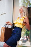 Happy young fashion woman with shopping bags at the mall window Stock Images