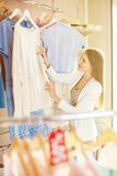 Young shopper. Elegant girl looking for new pullover in clothing department Stock Image