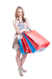 Young shopper with gift bags holding finger crossed. Looking hopeful and smiling isolated on white background Stock Photography