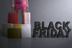 Young shopper holding shopping bag standing with Black Friday te Stock Images