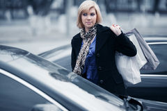 Young fashion woman with shopping bags next to her car Stock Images