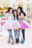 Young shoppers looking shopping bag. Group of teenage girls looking at shopping bags of their friend in the shopping center Stock Image