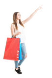 Young shopping female with paper bags pointing finger up Stock Photo