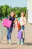 Young shopping twins girls with shopping bags have fun at the street Stock Images