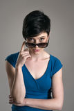 Young short hair brunette beauty peeking at camera above sunglasses. Over gray studio background Royalty Free Stock Images