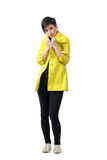 Young short hair brunette freezing covering neck with yellow rain coat. Royalty Free Stock Photography
