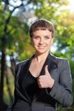 Young short hair woman in formalwear showing her thumb up. Good job! Happy young short hair caucasian woman in formalwear showing her thumb up and smiling while Royalty Free Stock Image