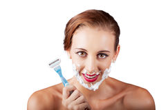 Funny portrait of a woman shaving face with razor Stock Photography