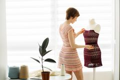 Young short-haired female designer using dress dummy at cozy home interior, freelance lifestyle stock images