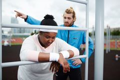 Young should go on training. Young trainer making plus-sized women work harder and motivating her to continue exercising Royalty Free Stock Images