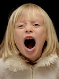Young shouting girl. A young blond girl, her mouth open wide as she shouts loudly, black background Stock Image