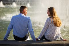 Young shy couple sitting near fountain holding hands at their f stock photos