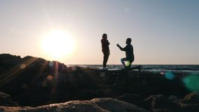 Young shy man making an offer to his beloved girl on the seashore at sunset. Attractive man standing on his knee and making an off