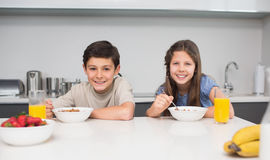 Young siblings enjoying breakfast in kitchen Royalty Free Stock Image