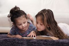 Two Little Sisters Reading Bible on Carpet Royalty Free Stock Image