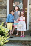 Young Siblings Outside Dressed Up for Easter holding Baskets. In front of home Stock Photos