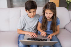 Young siblings using laptop in the living room Stock Images