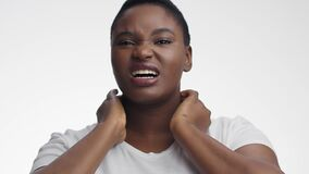 Young sick african american woman suffering from thyroid gland problem, touching her painful neck and grimacing