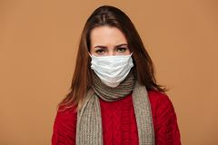 Young sick brunette woman in protective mask feeling bad over be Stock Images