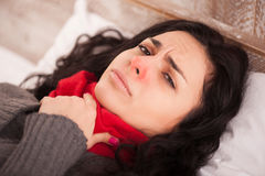 Young sick girl lying in bed. Sick woman with terrible sore throat. Closeup image of young woman with red nose lying in bed with thick scarf and touching her Royalty Free Stock Photography