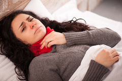 Young sick girl lying in bed Royalty Free Stock Images