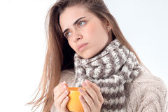 Young sick girl in the sweater holding a hot cup of tea isolated on white background Stock Image