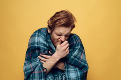 Young Sick Guy Wrapped in Checkered Plaid Sneezing royalty free stock photos