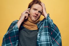 Young Sick Guy Wrapped in Plaid Talking Phone Stock Images