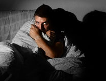 Young sick looking man suffering insomnia mental d. Young sick looking man sitting on couch at home in scary and desperate looking suffering insomnia, depression Stock Images
