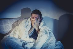 Young sick looking man suffering mental disorder or depression. Young sick man sitting on couch at home scary and desperate suffering insomnia, depression Stock Image