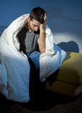 Young sick looking man suffering mental disorder or depression. Young sick man sitting on couch at home scary and desperate suffering insomnia, depression Royalty Free Stock Photo