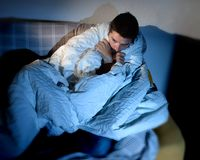 Young sick looking man suffering mental disorder o. Young sick looking man sitting on couch at home in scary and desperate looking suffering insomnia, depression Stock Image