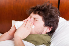 Young sick man blowing nose Stock Photos