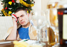 Young sick man with hangover and towel by head Royalty Free Stock Photo