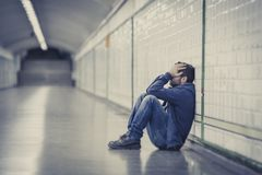 Young sick man lost suffering depression sitting on ground street subway tunnel. Young man drug addict homeless and abandoned lost in depression sitting on Royalty Free Stock Photo