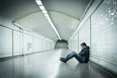 Young sick man lost suffering depression sitting on ground street subway tunnel Stock Photos