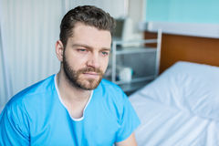 Young sick man sitting on hospital bed, hospital bed patient. Portrait of young sick man sitting on hospital bed, hospital bed patient royalty free stock images