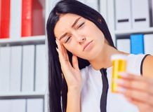 Young beautiful tired sick woman sitting in workplace in office holding bottle with pills. Female feeling bad at work. stock photo