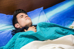 Young sick or unwell man in bed Stock Images