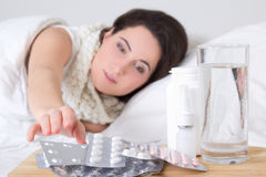 Young sick woman in bed and pills on the bedside table Stock Photography