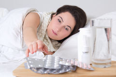 Young sick woman in bed and pills on the table Stock Photography