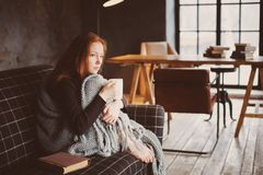 Young sick woman healing with hot drink at home on cozy couch. Wrapped in knitted blanket stock image
