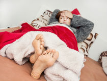 Young sick woman lying in bed Royalty Free Stock Image