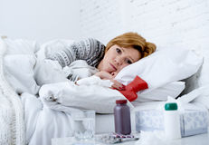 Young sick woman lying on bed ill feeling bad looking feverish and weak suffering winter flu virus Stock Images