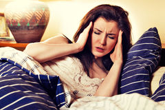 Young sick woman lying on her bed in bedroom Royalty Free Stock Photos
