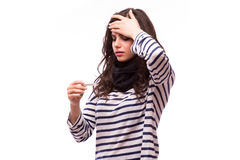 Young sick woman in scarf and home clothes looking at thermometer Stock Images