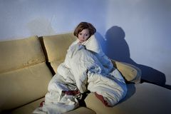 Young sick woman sitting on couch wrapped in duvet and blanket feeling miserable. Young depressed woman lying on couch wrapped in duvet and blanket feeling Stock Photo
