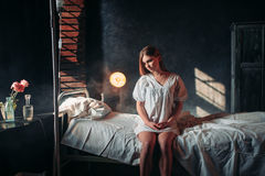 Young sick woman sitting on hospital bed on drip. Illness of female patient in clinic, health recovery and treatment Royalty Free Stock Photography